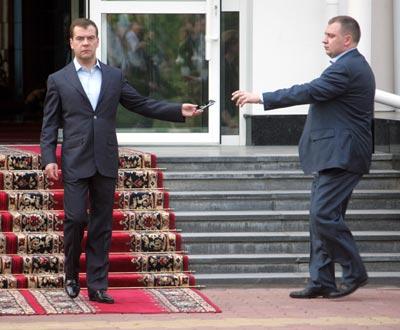 Президент Дмитрий Медведев отдает<br>солнцезащитные очки своему помощнику,<br>отправляясь встречать гостей - лидеров<br>Европейского Союза на саммите в Хабаровске.<br><br>Фото Константина Завражина